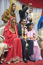 Bride;  groom and their families sitting together for blessing on their wedding day,