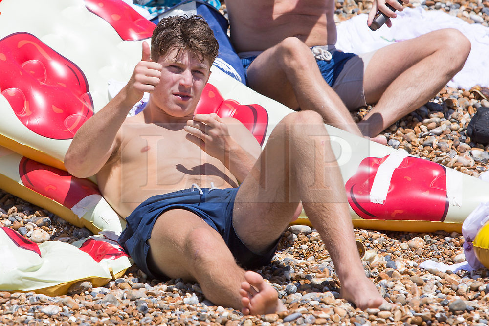 © Licensed to London News Pictures. 02/07/2017. Brighton, UK. Members of the public take advantage of the sunny weather to relax and sunbath on the beach in Brighton and Hove Photo credit: Hugo Michiels/LNP