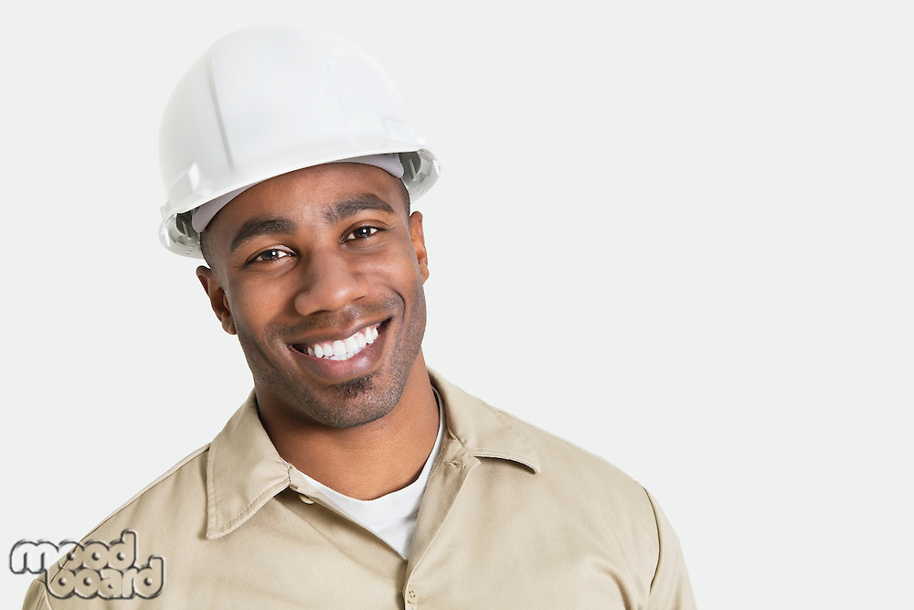 Portrait of happy African construction over with hardhat over gray background