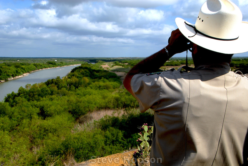 A Texas Game Warden watches the Rio Grande River which forms the U.S.-Mexico border, Zapata Texas, June 13, 2008.  In recent years, Texas' 1,248-mile border with Mexico has been the site of increased law enforcement problems as drug cartels, illegal alien smuggling and other crimes have become pronounced along border region. In response, the State of Texas and the U.S. government have stepped up the law enforcement presence in the remote and rugged region.