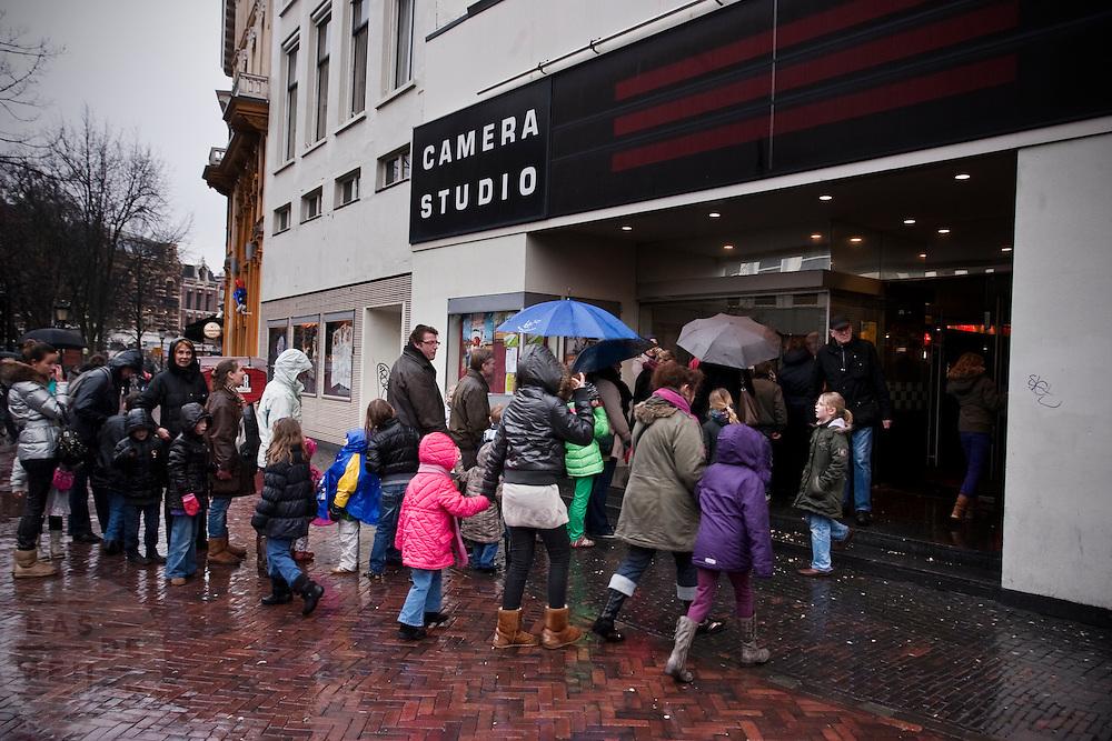 Ouders staan met hun kinderen op een regenachtige maandag in de vakantie in de rij voor de bioscoop in Utrecht