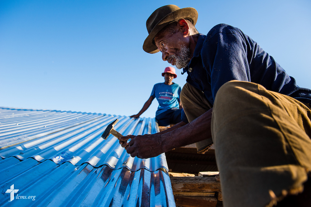 Falesoa Jean-Pierre (front) and Mahavita Arlin install a tin roof onto the Amboasary -1 Fiangonana Loterana Malagasy (FLM, Malagasy Lutheran Church) church near Amboasary, Madagascar, on Wednesday, Oct. 22, 2014. LCMS Communications/Erik M. Lunsford