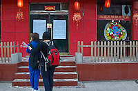 China, Beijing, Chaoyang, San Jian Fang, 2008. Students note a neighborhood restaurant's cry for help. The wreath in the window is traditionally reserved for funerals.