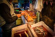 A seller skins some eels for sale.