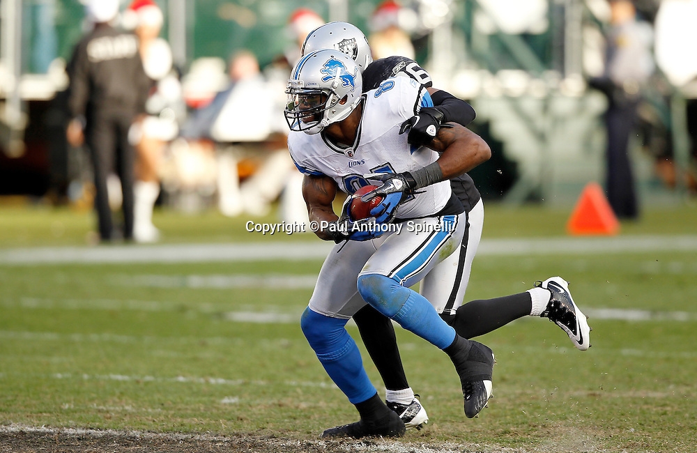 Detroit Lions wide receiver Calvin Johnson (81) catches a third quarter pass for a first down while trying to avoid a tackle attempt by Oakland Raiders cornerback Stanford Routt (26) during the NFL week 15 football game against the Oakland Raiders on Sunday, December 18, 2011 in Oakland, California. The Lions won the game 28-27. ©Paul Anthony Spinelli