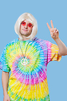 Portrait of funky young man gesturing peace sign against blue background