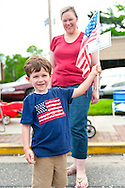 Young boy waving American Flag while watching Merrick Memorial Day Parade on May 28, 2012, on Long Island, New York, USA. America's war heroes are honored on this National Holiday.