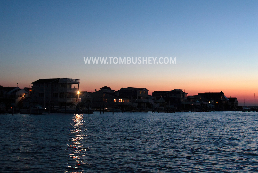 Beach Haven, NJ - The light on a deck shines across Little Egg Harbor Bay at Venus shines in the twilight sky on Long Beach Island on July 12, 2007.