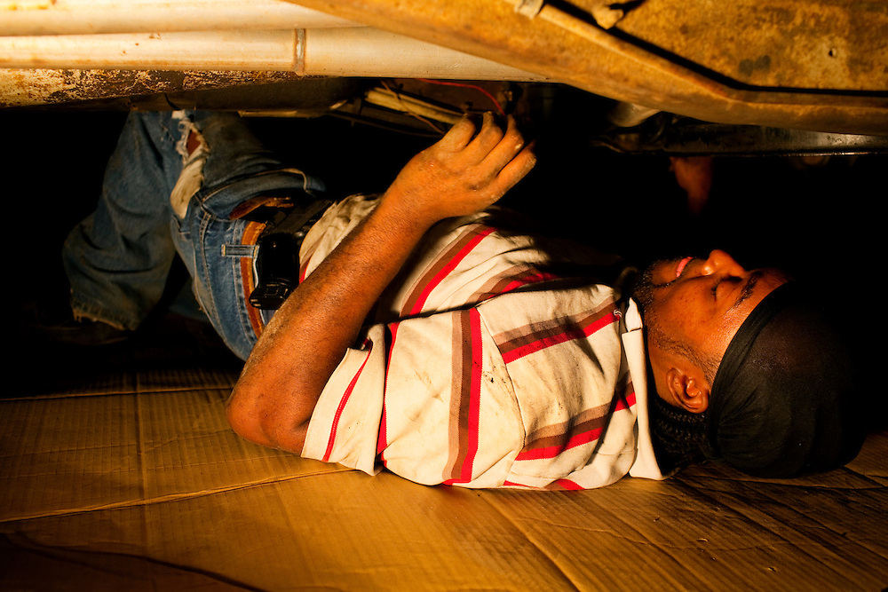 Nehemiah Hawkins works late at night to repair a car at his father's auto shop, just over the tracks from the Baptist Town neighborhood of Greenwood, Mississippi on February 16, 2011. Barely visible but tucked into his pants for safety is a handgun.