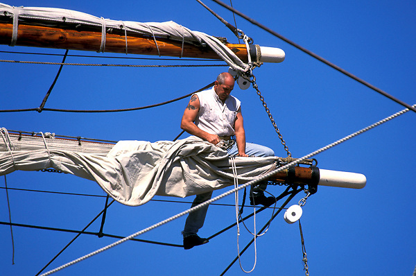 Man working on the sail of a large boat