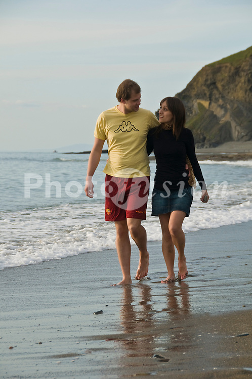 Young couple walking paddling in the sea Aberystwyth beach; Cadigan Bay; Wales