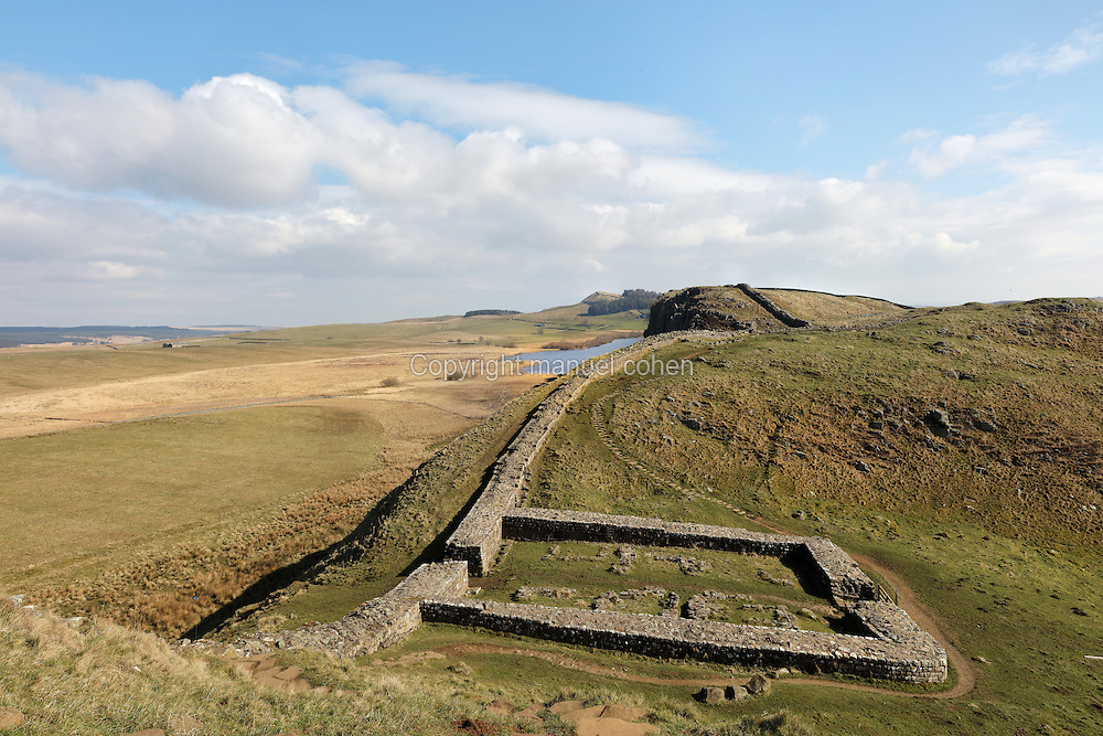 Milecastle 39, Castle Nick, near Steel Rigg on Hadrian's Wall, with Crag Lough in the distance, Northumberland, England. Hadrian's Wall was built 73 miles across Britannia, now England, 122-128 AD, under the reign of Emperor Hadrian, ruled 117-138, to mark the Northern extent of the Roman Empire and guard against barbarian attacks from the Picts to the North. The wall was fortified with milecastles with 2 turrets in between, and a fort about every 5 Roman miles. This section of the Wall is in the Northumberland National Park, managed by the National Trust, and the Hadrian's Wall Path, an 84-mile coast to coast long distance footpath, runs alongside it, together with a section of the Pennine Way. Picture by Manuel Cohen