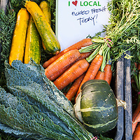 "Locally grown carrots, kale, squash and zucchini at a farmers market, with a sign that says ""I Heart Local: Picked Fresh Today"""