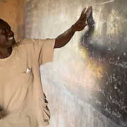 A French teacher writes on the board during class at the Savelugu Junior Secondary School in Savelugu, Ghana on Tuesday June 5, 2007..