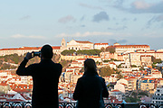 Silhouettes of tourists and visitors admiring the view of Lisbon from St. Peter's observation point (Miradouro de Sao Pedro de Alcantara) in the Bairro Alto, Lisbon, Portugal