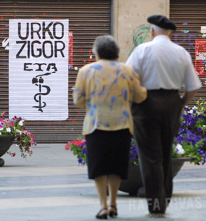 An elder couple walk past a poster with symbol of separatist armed Basque terrorist group ETA and te name of two dead activists, on August 11, 2001 i the Basque town of Durango, north of Spain. Photo Rafa RIVAS