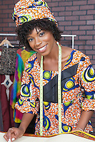 Portrait of an attractive African American female fashion designer working on fabric