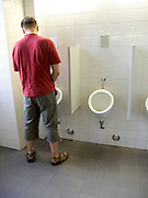 Man using a urinal in a men's public lavatory