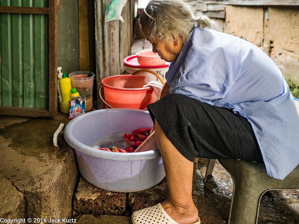 07 SEPTEMBER 2016 - BANGKOK, THAILAND:  A woman does her laundry on the sidewalk in front of her home in the Pom Mahakan community. Forty-four families still live in the Pom Mahakan Fort community. The city of Bangkok has given them provisional permission to stay, but city officials say the permission could be rescinded and the city go ahead with the evictions. The residents of the historic fort have barricaded most of the gates into the fort and are joined every day by community activists from around Bangkok who support their efforts to stay.      PHOTO BY JACK KURTZ