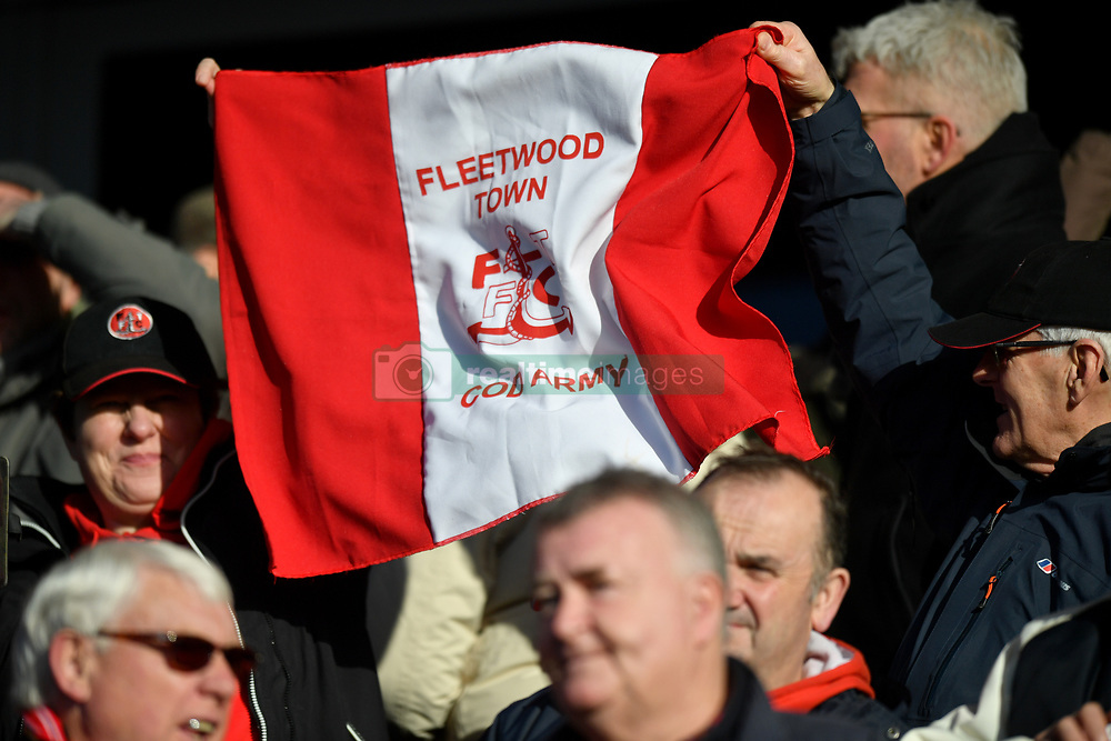 Fans in the stands with a Fleetwood Town Cod Army flag