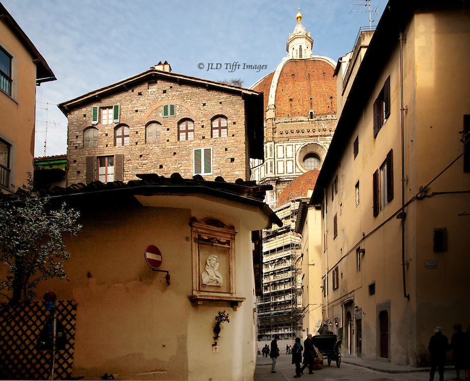 Narrow medieval streets of the historical district in Florence offer occasional partial looks at the famous dome of the Duomo, or Cathedral.