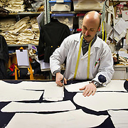 VENICE, ITALY - JANUARY 20: Master tailor Francesco Briggi of the historic atelier Pietro Longi cuts some garments for military costumes on January 20, 2012 in Venice, Italy. This is one of the busiest periods of the year for the atelier as the next few weeks the streets and canals of Venice will be filled with people attending the carnival,  wearing highly-decorative and imaginative carnival costumes and masks.