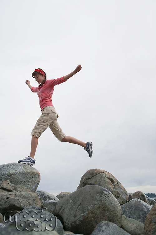 Woman with arms outstretched jumping on rocks