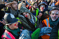 London, UK. 17th November, 2018. A troupe of clowns mimics a police arrest as they support environmental campaigners from Extinction Rebellion blocking Lambeth Bridge, one of five bridges blocked in central London, as part of a Rebellion Day event to highlight 'criminal inaction in the face of climate change catastrophe and ecological collapse' by the UK Government as part of a programme of civil disobedience during which scores of campaigners have been arrested.