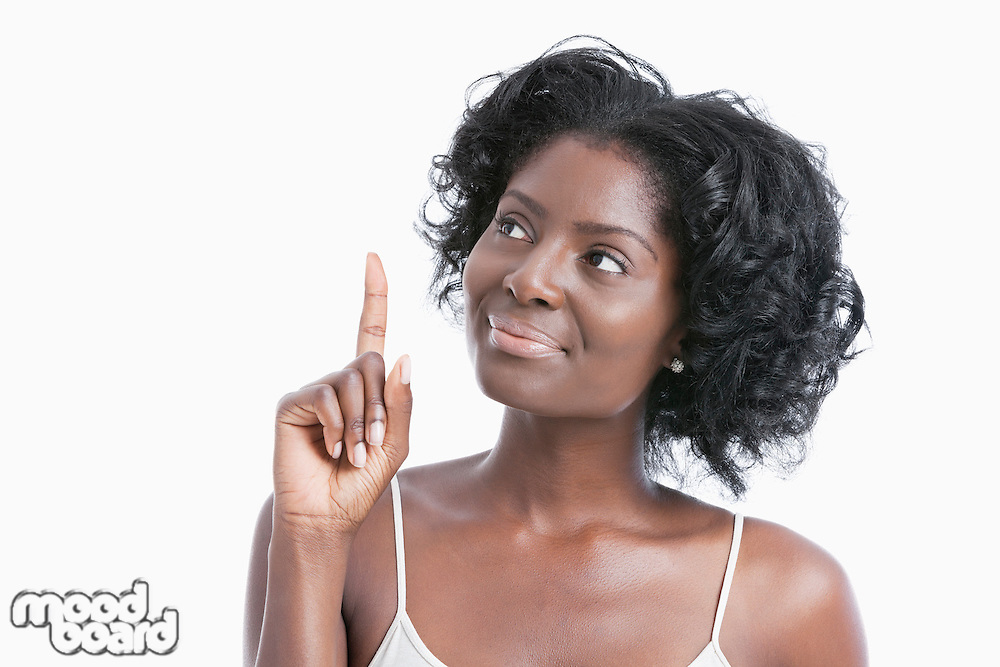 African American young woman pointing her index finger upwards over white background
