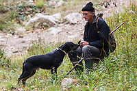 Romanian man helping as a driver during a driving hunt for Wild boar (Sus scrofa) and his dog in the forest area outside the village of Mehadia, Caras Severin, Romania.