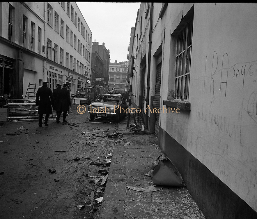 Car Bomb Damage in Dublin (E10)..1972.02.12.1972..12.02.1972..2nd December 1972..On the morning of 2nd December '72 two car bombs exploded in Dublin City. At Sackville Place two busmen were killed as they waited in their car to resume work. The busmen were named as George Bradshaw (30) and Thomas Duffy (23). The bomb was thought to be planted by a Northern Ireland subversive group who hoped to influence legislation going through Dail Eireann in relation to the I.R.A...Image of Gardai closing off the street at the scene of the fatal explosion where the two busmen lost their lives.