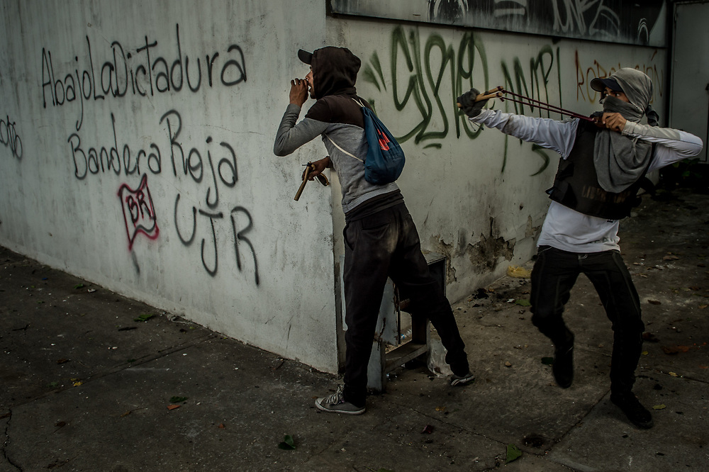 CARACAS, VENEZUELA - JULY 26, 2017: Members of La Resistencia use slingshots to launch rocks at soldiers, who responded with tear gas, rubber bullets and buckshot, during an anti-government protest to demand that the National Constituent Assembly election scheduled for Sunday, July 30th be cancelled. The political opposition called for a 48 hour national strike on July 26th and 27th, and for their supporters to close businesses, not go to work, and instead create barricades to block off their streets.  Opposition controlled areas of the country were completely shut down.  The strike was called as part of the opposition's civil resistance movement - that began on April 1st, to protest against the Socialist government's attempt to elect a new assembly that will have the power to re-write the constitution, and their opposition to the Socialist's continued threats to Venezuelan Democracy.  PHOTO: Meridith Kohut for The New York Times
