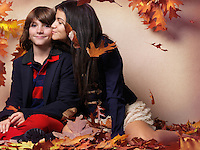 Teenage girl kissing a boy sitting surrounded with red autumn leaves artistic childrens fall fashion and lifestyle photo