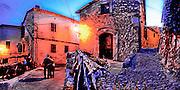 An old couple strolls a narrow street in Valdemossa on Majorca, balearic Islands, Spain