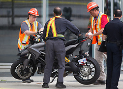 "Officials from WorkSafeBC and a tow truck operator, front, move a motorcycle after a female stunt driver working on the movie ""Deadpool 2"" died after a crash on set, in Vancouver, BC, Canada, on Monday August 14, 2017. Vancouver police say the driver was on a motorcycle when the crash occurred on the movie set on Monday morning. Photo by Darryl Dyck/CP/ABACAPRESS.COM"