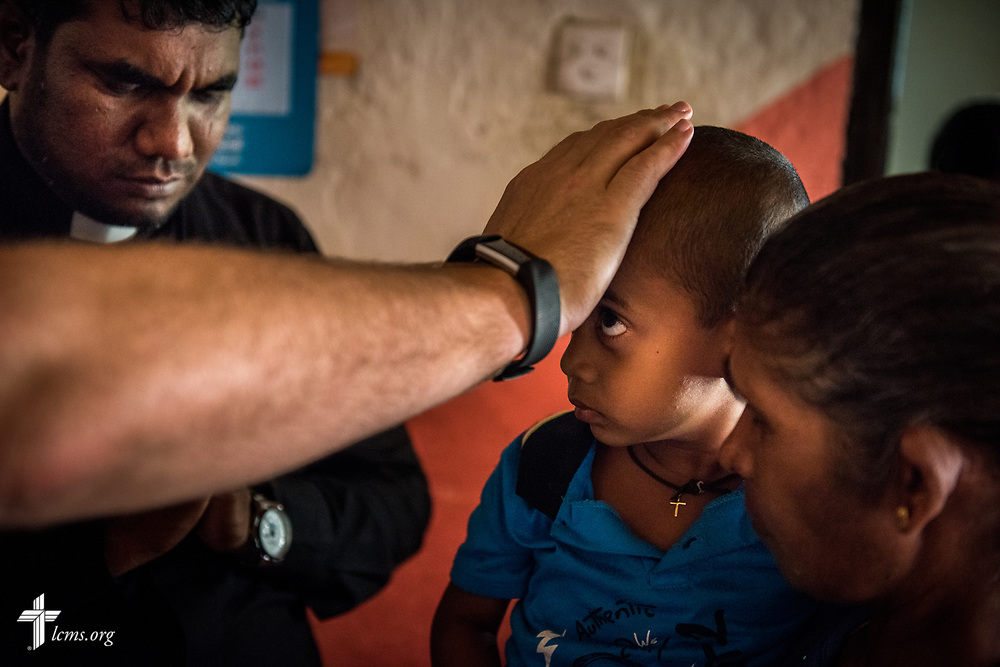 The Rev. P. Gnanakumar and the Rev. Steven Mahlburg, LCMS career missionary to Sri Lanka, prays for a sick child during home visitations with church members on the Eila rubber plantation in the Sabaragamuwa Province of Sri Lanka on Saturday, Jan. 20, 2018. LCMS Communications/ Erik M. Lunsford