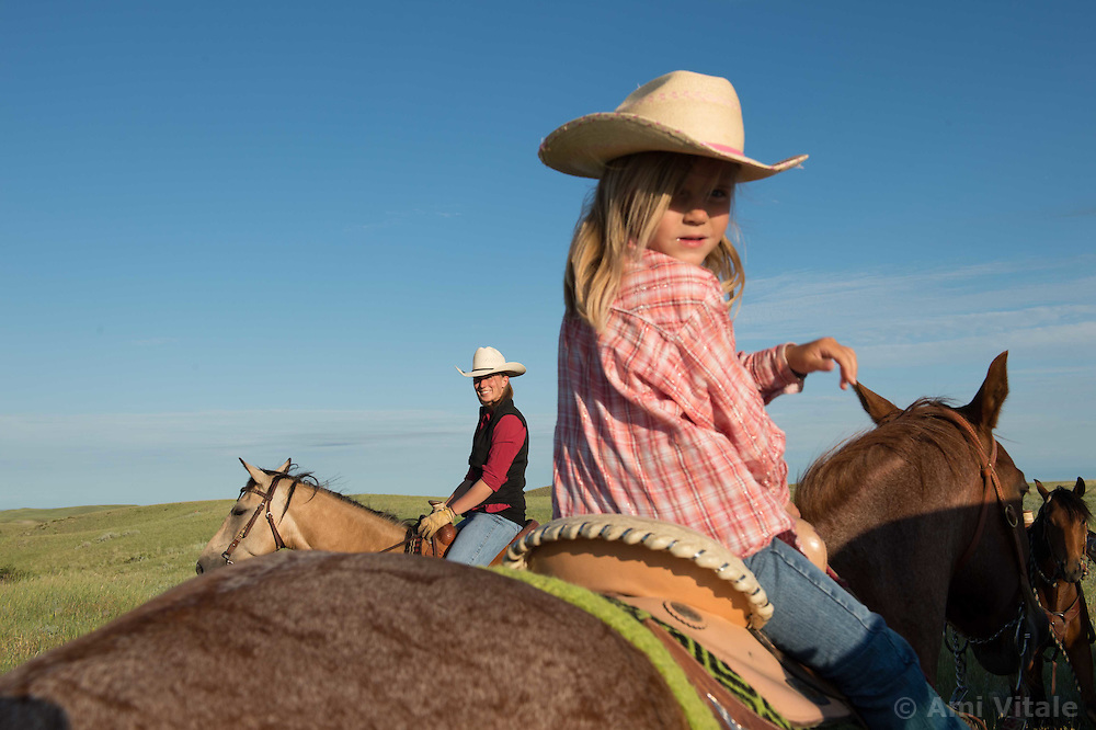 Layla Messerly, the daughter of the Nature Conservancy's Matador Ranch Operations Manager Charlie Messerly helps her dad work with 13 ranching families in Eastern Montana  at the Matador ranch &quot;grass bank&quot;. The &ldquo;grass bank&quot; is an innovative way to leverage conservation gains, in which ranchers can graze their cattle at discounted rates on Conservancy land in exchange for improving conservation practices on their own &ldquo;home&rdquo; ranches. In 2002, the <br /> Conservancy began leasing parts of the ranch to neighboring ranchers who were suffering from  severe drought, offering the Matador&rsquo;s grass to neighboring ranches in exchange for their  participation in conservation efforts. The grassbank has helped keep ranchers from plowing up native grassland to farm it; helped remove obstacles to pronghorn antelope migration; improved habitat for the Greater Sage-Grouse and reduced the risk of Sage-Grouse colliding with fences; preserved prairie dog towns and prevented the spread of noxious weeds. (Photo By Ami Vitale)