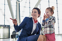 Portrait of airport staff playing with cute little girl in airport