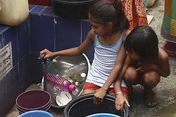 April 25, 2018 - Kolkata, West Bengal, India - Indian girls at slums holds water supply pipe and wait for water due to water scarcity with advent of summer. The advent of summer in West Bengal and India brought heat wave like conditions with the increasing temperature record in the country. (Credit Image: © Saikat Paul/Pacific Press via ZUMA Wire)