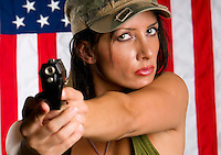 Young woman wearing military uniform pointing with gun. Use of selective focus. Focus in woman.