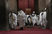 Ethiopian Orthodox Christian priests pray inside a rock-hewn church in Lalibela. Located at 2,500 meters above sea level, Lalibela is one of Ethiopia's holiest cities and a center of pilgrimage for the Ethiopian Orthodox Christian population. Declared a UNESCO World Heritage Site, Lalibela's rock-hewn churches were built in the 12th and 13th centuries and are said to represent a miniature version of Jerusalem. Lalibela, Amhara Division, Ethiopia. March 31, 2011.