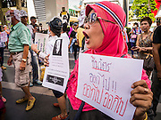"09 JUNE 2013 - BANGKOK, THAILAND: A Thai Muslim woman who is a member of the White Masks protests against the government of Yingluck Shinawatra at Central World. The White Mask protesters wear the Guy Fawkes mask popularized by the movie ""V for Vendetta"" and the protest groups Anonymous and Occupy. Several hundred members of the White Mask movement gathered on the plaza in front of Central World, a large shopping complex at the Ratchaprasong Intersection in Bangkok, to protest against the government of Thai Prime Minister Yingluck Shinawatra. They say that her government is corrupt and is a ""puppet"" of ousted (and exiled) former PM Thaksin Shinawatra. Thaksin is Yingluck's brother. She was elected in 2011 when her brother endorsed her.      PHOTO BY JACK KURTZ"