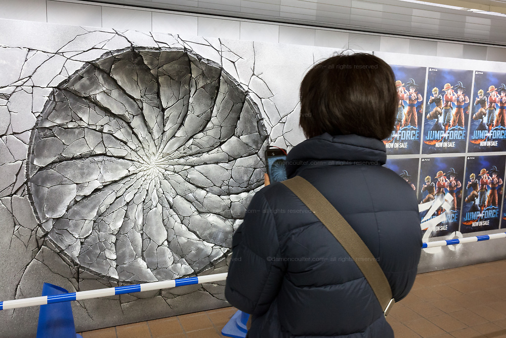 A woman takes a photo of one of three craters in a wall advertising the Jump Force video game for Play Station, X-box and Window PC in Shinjuku Station, Tokyo, Japan. Friday February 22nd 2019. Jump Force  game brings together all the most popular characters from the Shonan Jump manga comics.and was released on February 15th. The punch wall represents the effect of a power punch from characters Son Goku of Dragonball, Naruto and Luffy from One Piece and runs to February 24th