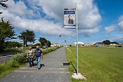 May 30, 2019, Utah Beach,  Normandy, France. A man and a woman walk beneath a portrait of a fallen US soldier in 1944 during the 75th anniversary of D-Day and Battle of Normandy commemorations. <br /> 30 Mai 2019, Utah Beach, Normandie, France. Un homme et une femme marchent sous le portrait d'un soldat américain tombé au combat en 1944 pendant le 75e anniversaire des commémorations du jour J et de la bataille de Normandie.