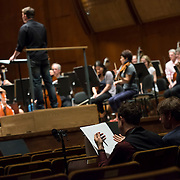 June 3, 2014 - New York, NY : As part of the New York Philharmonic Biennial, the orchestra solicited pieces from little-known composers and will choose three to play. Pictured here, conductor-composer Matthias Pintscher, on podium, leads the New York Philharmonic as it performs a composition by Andrew McManus, who is visible at foreground left, working with mentor composer Steven Mackey, on Tuesday. CREDIT: Karsten Moran for The New York Times