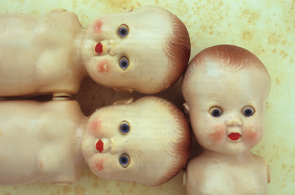 Faces and limbless bodies of three identical vintage baby dolls with big staring blue eyes and red lips and slightly scuffed and soiled