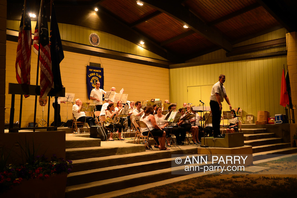 Port Washington, New York, U.S. - July 11, 2014 - Band conductor takes bow at end of night time community band concert at John Philips Sousa Memorial Band Shell, outdoors at Sunset Park on Manhasset Bay, on the North Shore village on Long Island Gold Coast.