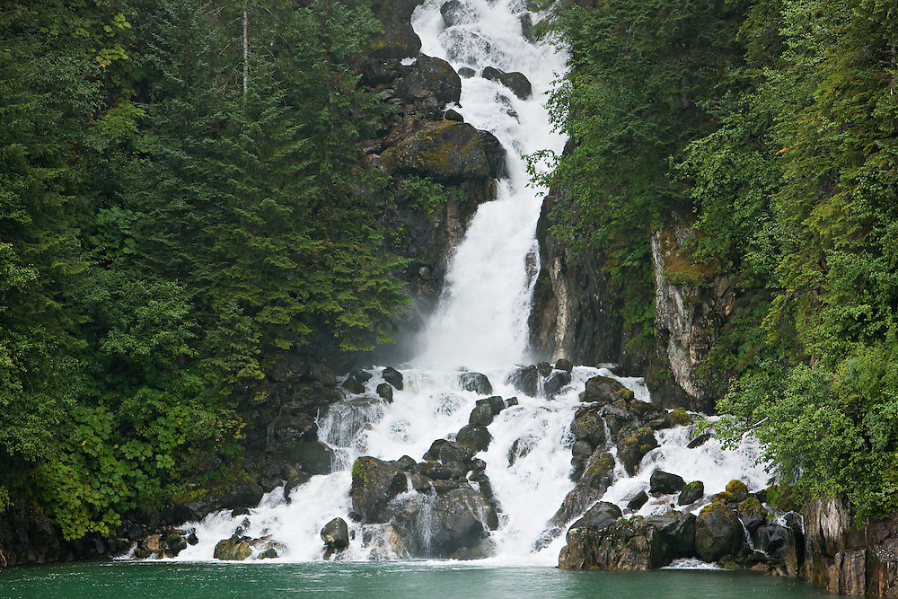Waterfall in the Tongass National Forest carrying fresh water to the salt water of the Endicott Arm fjord of Tracy Arm - Fords Terror Wilderness.  Southeast.  Inside Passage.  Summer.  Afternoon.