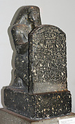 Statue of Montuemhat kneeling and holding up a stele. 25th or 26th Dynasty (approx. 670-650 BC) Egyptian. Made from Granodiorite. The stele shows the prophet Montuemhat offering to Atum-Khepri, and contains text from the Book of the Dead.