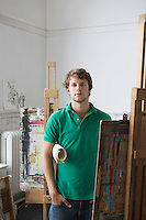 Portrait of young male artist in art studio